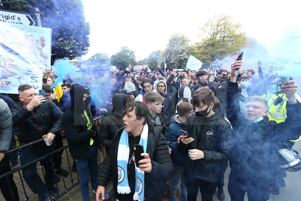 © Licensed to London News Pictures. 23/05/2021. Manchester, UK.  Man City fans let off flares to celebrate winning the Premier League. Thousands of supporters have gathered at the Etihad Stadium to celebrate winning their 5th Premier League title in 10 years.  Photo credit: Adam Vaughan/LNP