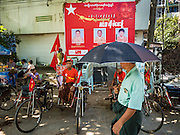 02 NOVEMBER 2015 - YANGON, MYANMAR: A man carrying an umbrella walks past pedicab drivers wearing NLD tee shirts wait for fares under a NLD poster in Yangon. National elections are scheduled for Sunday Nov. 8 in Myanmar. The two principal parties are the National League for Democracy (NLD), the party of democracy icon and Nobel Peace Prize winner Aung San Suu Kyi, and the ruling Union Solidarity and Development Party (USDP), led by incumbent President Thein Sein. There are more than 30 parties campaigning for national and local offices. PHOTO BY JACK KURTZ