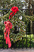 A wrought iron garden gate of a historic home decorated with a Christmas wreath on Meeting Street in Charleston, SC.