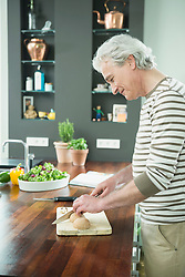 Mature man cutting vegetable on chopping board in kitchen, smiling