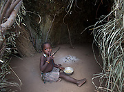 A young girl eating Baobad fruit at the Hadza camp of Senkele.