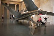 Visitors ponder the installation of artist Fiona Banner's fighter jet art work 'Harrier and Jaguar' which is exhibited in the north Duveens gallery at Tate Britain, London. This Sepecat Jaguar aircraft was once in service with the Royal Air Force (RAF). It's serial number was XZ118 and its first  was in 1976 and its last in 2006. Its insertion into the gallery was by dismantling the fuselage and re-assembling in situ. Its nose points a few inches from the ground and we see it's now empty cockpit. Banner's art is concerned with flying machines of war that flow low over her as a child in Wales. They may be machines of war but also have the personalities of hanging or submissive birds or beasts, nudes or totems, provoking the idea of body and machine in intimate confrontation. The show runs 28 June 2010 – 3 January 2011.