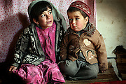 Monirah, 7, (Left) and her brother Najibullah, 3, (Right) are sitting in the cave where their family now live since six years in Bamyan, central Afghanistan, an area mostly populated by Hazaras. A historically persecuted minority (15%) due to more lenient Islamic faith and characteristic 'Eastern' lineaments, Hazaras constitute the 70% of Bamyan's population.