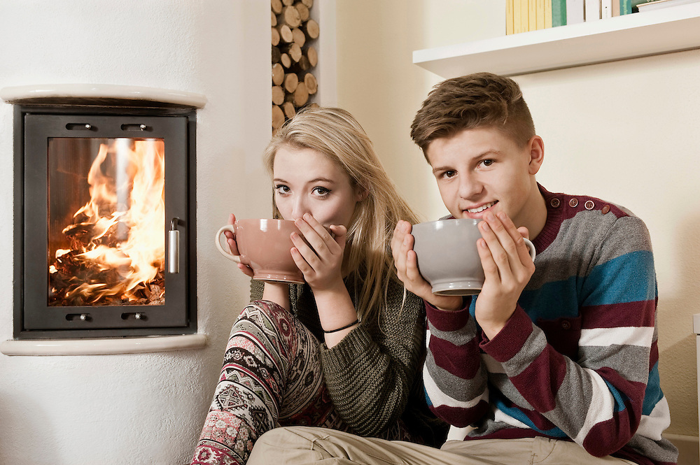 Teenage couple drinking hot beverages in front of fireside