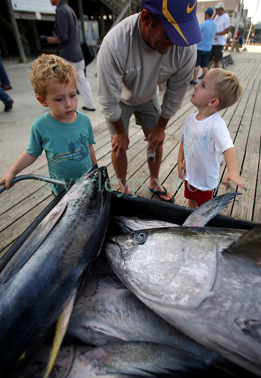 07 May 2010. Venice, Louisiana. Deepwater Horizon, British Petroleum environmental oil spill disaster.<br /> L/R; Locals Ben Varley (3yrs), Bobby Warren and Evan Ballay (3 yrs) admire yellow fin tuna and other predator species caught by sport fishermen to the west of the giant BP oil spill. Nobody is sure how much longer they will be able to catch fish in the region. Charter boat captains, rental camps and hotels are reporting mass cancellations of fishing trips and other vacations to the Gulf  Coast region.<br /> Photo credit; Charlie Varley/varleypix.com