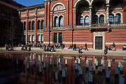 Visitors outside in the sunshine at The John Madejski Garden. The Victoria and Albert Museum aka the V&A at South Kensington, London. Known as the world's greatest museum of art and design, with collections unrivalled in their scope and diversity. Discover 3000 years' worth of amazing artefacts from many of the world's richest cultures including ceramics, furniture, fashion, glass, jewellery, metalwork, photographs, sculpture, textiles and paintings.