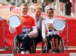 Great Britain's David Weir (left) and Australia's Madison de Rozario pose with their trophies after and Prince Harry during the 2018 Virgin Money London Marathon.