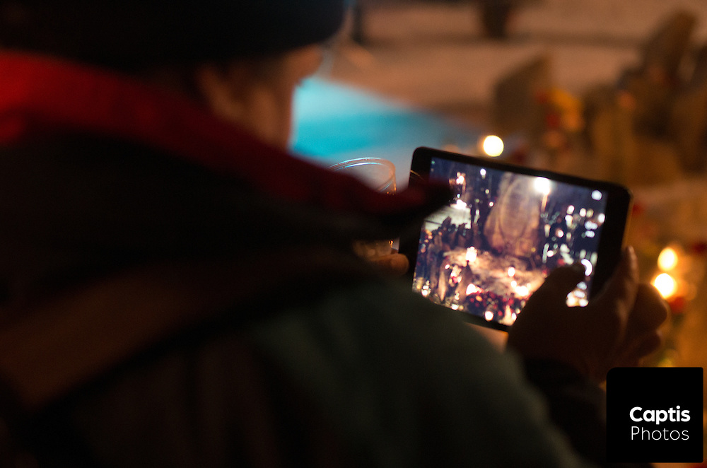 An attendant of the vigil takes a photo of the Women's Monument on an iPad. December 6, 2014.