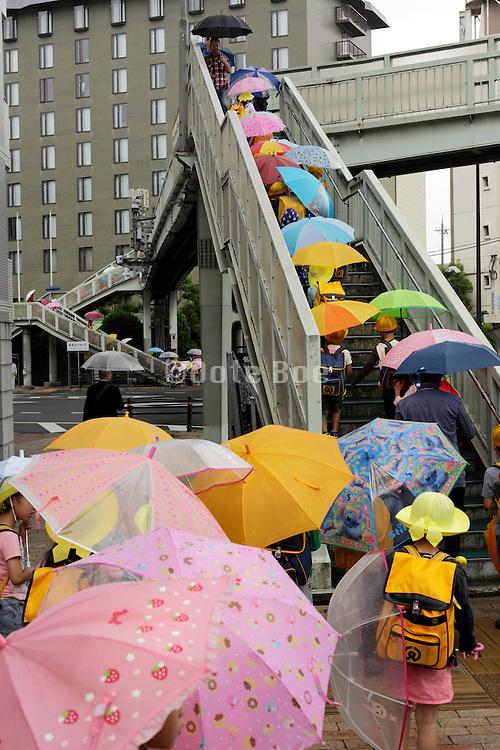 little school children with bright colored umbrellas using a cross over bridge Kyoto Japan