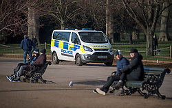 © Licensed to London News Pictures. 07/01/2021. London, UK. Police drive past people sat on park benches as they patrol in Hyde Park in central London, during a third national Lockdown, during which members of the public are only permitted to leave their homes for essential activities or to exercise once a day.. Photo credit: London News Pictures.