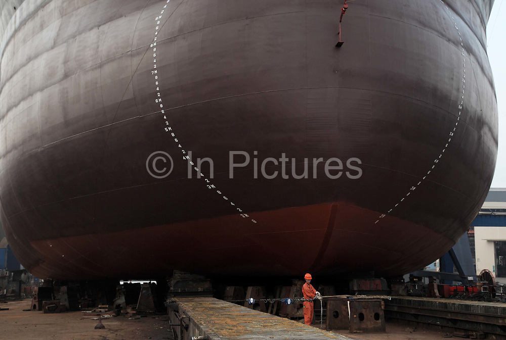Workers make final preparation before launching the 57,000 dead weigh ton bulk carrier Sabina Venture into the Yangzte River at the China CSSC Holdings Ltd. Chengxi Shipyard in Jiangyin, China, on Sunday, Sept. 12, 2010. China CSSC Holdings Ltd., the nation's biggest shipyard, sees orders surge as China's voracious appetite for commodities demands more fleets of large vessels.