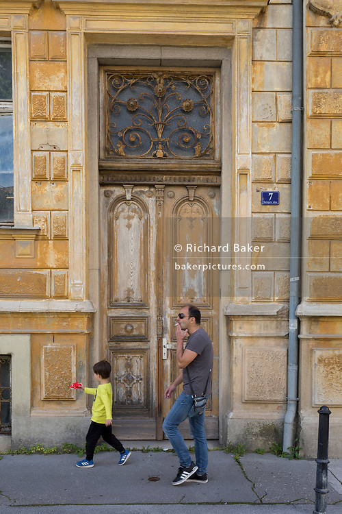 A smoking man and child walk past an old doorway and architecture, on 23rd June 2018, in Celje, Slovenia.