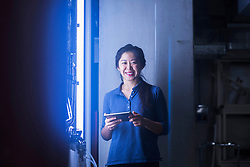 Young female engineer using digital tablet and smiling in an industrial plant, Freiburg im Breisgau, Baden-Wuerttemberg, Germany