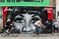 © Licensed to London News Pictures. 19/08/2018. London, UK.  Cyclists and a pedestrian pass new street art in Shoreditch, east London, paying tribute to the singer, Aretha Franklin who has died following a battle with pancreatic cancer.  The mural has been created by artist, Jules Muck in collaboration with Global Street Art. Photo credit: Vickie Flores/LNP