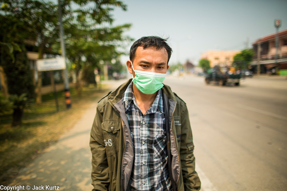 """09 APRIL, 2013 - DO SAKET, CHIANG MAI, THAILAND:  A Shan hilltribe man walks along the highway in Doi Saket to a nearby hospital. He said he was going to the hospital because he couldn't breathe because of the smoke in the air. He said that was also why he was wearing the breathing mask. The """"burning season,"""" which roughly goes from late February to late April, is when farmers in northern Thailand burn the dead grass and last year's stubble out of their fields. The burning creates clouds of smoke that causes breathing problems, reduces visibility and contributes to global warming. The Thai government has banned the burning and is making an effort to control it, but the farmers think it replenishes their soil (they use the ash as fertilizer) and it's cheaper than ploughing the weeds under.     PHOTO BY JACK KURTZ"""