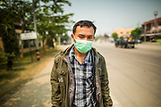 "09 APRIL, 2013 - DO SAKET, CHIANG MAI, THAILAND:  A Shan hilltribe man walks along the highway in Doi Saket to a nearby hospital. He said he was going to the hospital because he couldn't breathe because of the smoke in the air. He said that was also why he was wearing the breathing mask. The ""burning season,"" which roughly goes from late February to late April, is when farmers in northern Thailand burn the dead grass and last year's stubble out of their fields. The burning creates clouds of smoke that causes breathing problems, reduces visibility and contributes to global warming. The Thai government has banned the burning and is making an effort to control it, but the farmers think it replenishes their soil (they use the ash as fertilizer) and it's cheaper than ploughing the weeds under.     PHOTO BY JACK KURTZ"