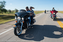 Robbie and Penny Gale on their 2005 Electra Glide riding south on highway 79 on the Run to the Line after lunch and the biker vs Cowboy rodeo games at the Spur Creek Ranch in Newell during the annual Sturgis Black Hills Motorcycle Rally. SD, USA. Wednesday August 9, 2017. Photography ©2017 Michael Lichter.