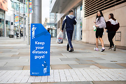 © Licensed to London News Pictures. 20/10/2020. Manchester, UK. A group walks past a sign in Manchester reminding people to keep your distance. Manchester is expecting to be forced in to a Tier 3 lockdown unless a deal is agreed. Photo credit: Kerry Elsworth/LNP
