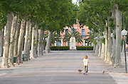 Village square with woman walking dogs and Marechal Joffre statue. Rivesaltes town, Roussillon, France