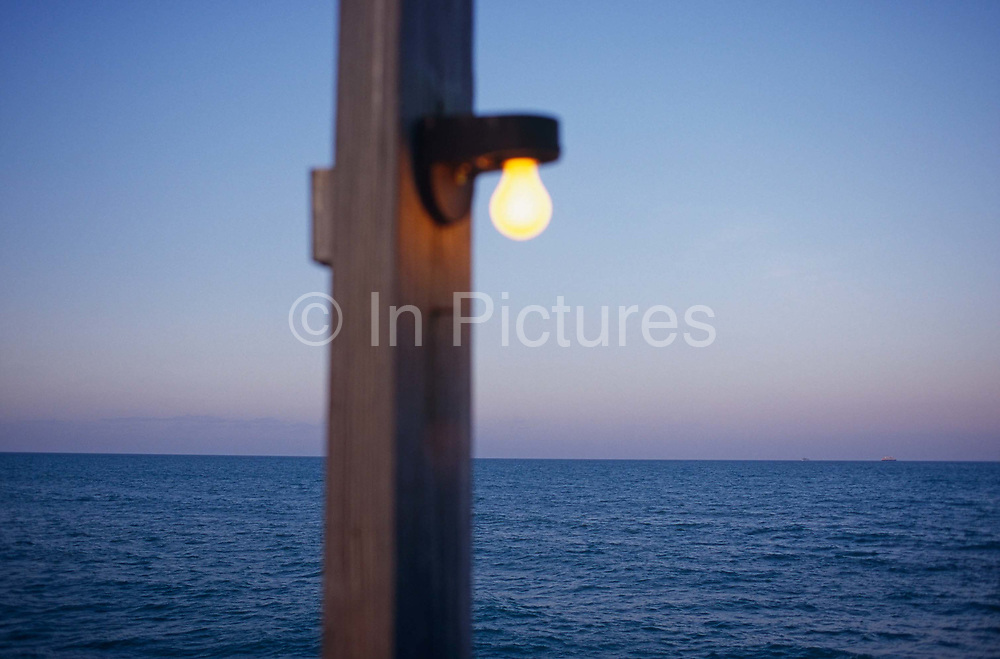 """An out of focus post with a light bulb attached, shines in the bright daylight with the Atlantic Ocean beyond. Cocoa beach is on Florida's so-called Space Coast, a resort of beaches, clubs, seafood restaurants and motels that came to life during the 1960s due to America's space program. NASA's John F. Kennedy Space Center is located approximately 15 miles away. The Atlantic Ocean is flat calm in settled weather and the horizon is clear and well-defined with a ship just visible on the right side. Focus is on the sea rather than the post and the light bulb which look like a surreal addition to the landscape. Cocoa Beach served as a playground for many of the astronauts and NASA space industry workers and contractors during the heyday of the space race. After manned space flights, the town held astronaut parades. Before there was a """"Silicon Valley,"""" Cocoa Beach and other surrounding towns were full of the best and brightest technical minds around."""