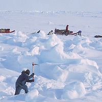 Team member chops path for dog sleds through a pressure ridge on Arctic Ocean.