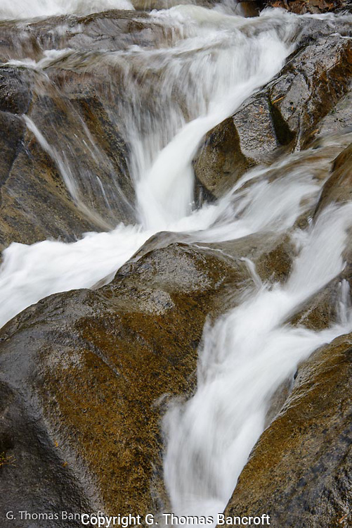 The water tumbled down through a series of crevices in the water smoothed rocks.  The water divided between water courses and came back together as it tumbled down the cascade.