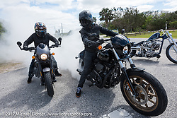 Having some fun burning rubber, custom bike builder Jesse Rooke on a new 2017 Harley-Davidson 750 Street Rod alongside his friend Anthony Paggio on a 2017 Harley-Davidson Milwaukee-Eight at the entrance to Tomoka State Park during Daytona Beach Bike Week. FL. USA. Tuesday, March 14, 2017. Photography ©2017 Michael Lichter.