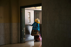 A traditionally dressed Andean woman peers down the hallway of the Hospital Regional del Cusco in Peru. The hospital is a critical lifeline for many of the region's indigenous residents and is the only public hospital in Cusco that offers pediatric surgery.