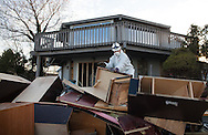 Union Beach NJ, November 16, Clean-up worker in a Hazmat suit working on a house on Front Street destroyed by superstorm Sandy's surge, that damaged over 200 homes in Union Beach alone. Hurricane Sandy's strength is being blamed on climate change by many scientists.