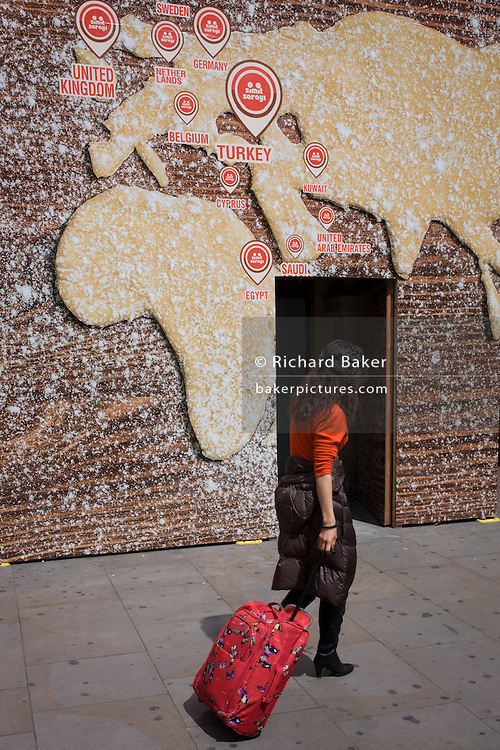 Tourist pulls baggage beneath a world map on a bakery business hoarding.