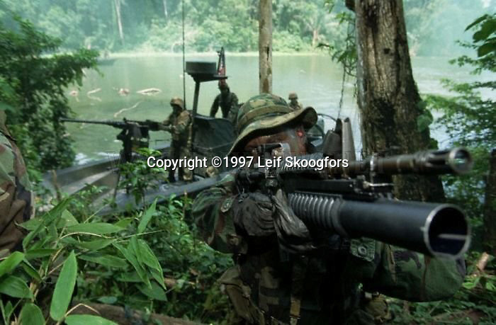 US Navy Special Warfare with M-16 and M-203 grenade launcher. Team lands ashore from modified Boston Whaler boat.