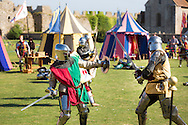 McG0064278<br /> Performers in heavy armour fight at Portchester Castle in Hampshire where events have been taking place to mark the 600th anniversary of the battle of Agincourt. <br /> In 1415 soldiers left from the castle, now managed by English Heritage, for northern France where they went on to face the French in a muddy farmer's field.<br /> Picture date: Saturday August 8, 2015.<br /> Photograph by Christopher Ison ©<br /> 07544044177<br /> chris@christopherison.com<br /> www.christopherison.com