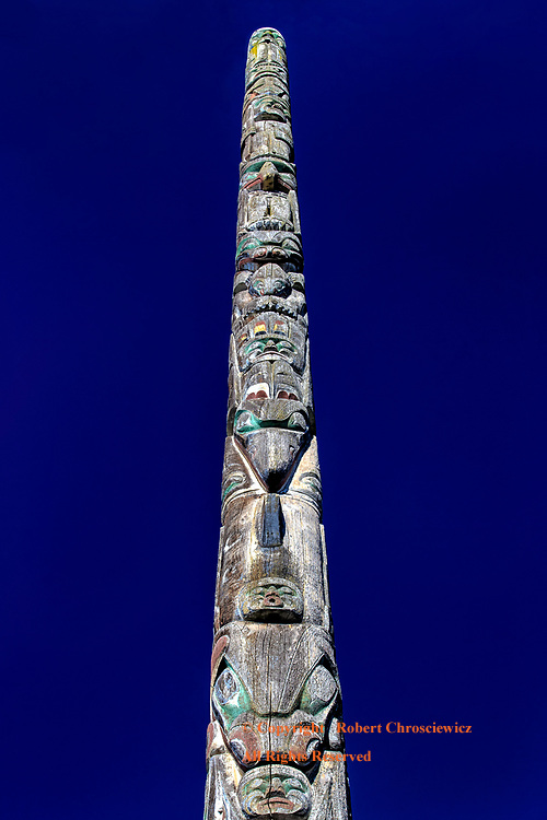 Totem on Blue: A bold, west coast-Native Indian, wooden totem pole splits a deep blue sky as it prominently displays carved birds of prey, frogs and bears, Vancouver British Columbia, Canada.