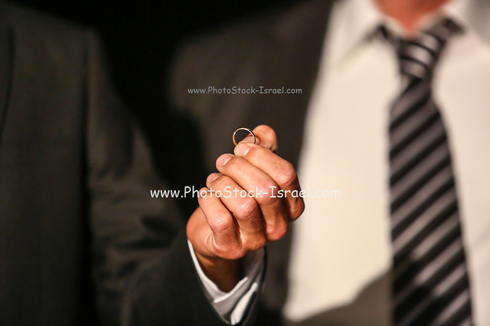 Best man hands the wedding band to the groom at a wedding