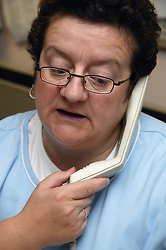 Call Centre Operator answering call into busy Hospital switchboard,