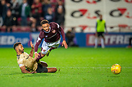Shay Logan (#2) of Aberdeen FC slides in and fouls Jake Mulraney (#11) of Heart of Midlothian FC during the Betfred Scottish Football League Cup quarter final match between Heart of Midlothian FC and Aberdeen FC at Tynecastle Stadium, Edinburgh, Scotland on 25 September 2019.