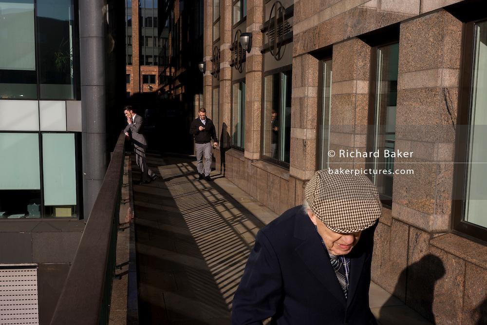 Elderly man walks along modern walkway, past a youthful office worker enjoying a thoughful moment in City of London.