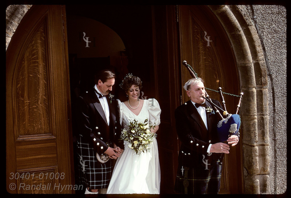 Bagpiper plays ceremonial tune as bride & groom walk out church doors after wedding; Anstruther. Scotland