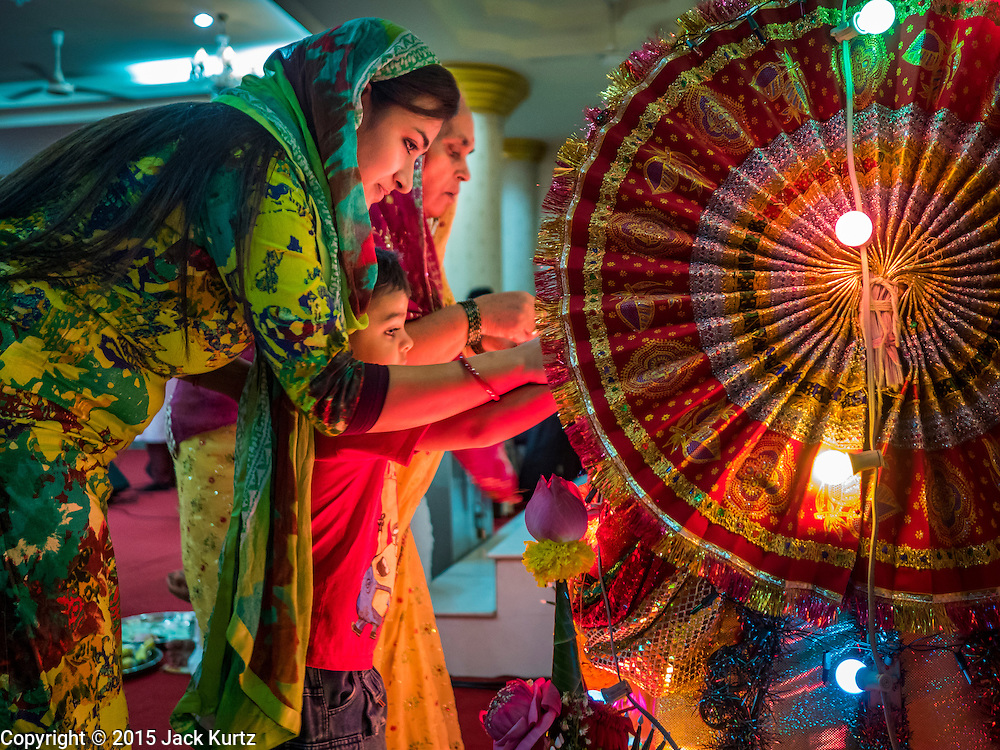 05 SEPTEMBER 2015 - BANGKOK, THAILAND:  Hindus in Bangkok look at the deity that represents Krishna in a crib during Janmashtami services at the Vishnu Temple in Bangkok. Janmashtami is the annual celebration of the birth of the Hindu deity Krishna, the eighth avatar of Vishnu. Hindus celebrate Janmashtami by fasting, worshipping Krishna and staying up until midnight, the time when Krishna is believed to have been born. At midnight they pray and exchange small gifts.    PHOTO BY JACK KURTZ