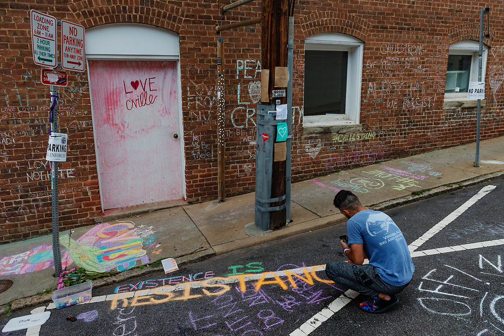 """Ahmed Mohamed writes """"Resistance"""" in chalk on the ground of the alleyway where Heather Heyer's memorial is located on the second anniversary of the """"Unite the Right"""" rally in Charlottesville, W.V. on Saturday, August 11, 2018. Heyer was killed and 19 others injured when an alleged neo-nazi plowed his vehicle into a crowd of counter-protesters during the first """"Unite the Right"""" rally on August 12, 2017."""