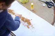 Child's handcraft glueing sand on paper