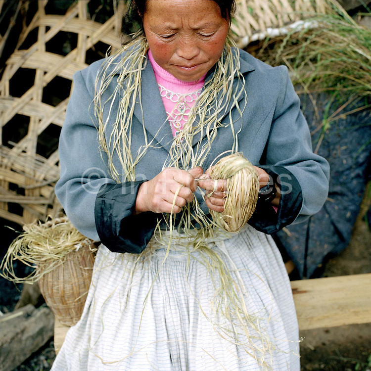 """Wearing a traditional hemp skirt, a Big Flowery Miao ethnic minority woman splices hemp, Qie Chong village, Guizhou Province, China. Although hemp production is decreasing because land is needed for cash crops and manufactured cotton is readily available, it is still grown, spliced and women in remote mountain villages in Guizhou Province. Almost 35% of Guizhou's population is made up of over 18 different ethnic minorities including the Miao. Each Miao group became isolated in these mountainous regions, hence the present day diversity in their culture, costume and dialects. According to a popular saying, """"if you meet 100 Miaos, you will see 100 costumes."""""""