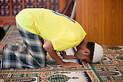 """Sept. 24, 2009 -- PATTANI, THAILAND: Muslim men pray at Krue Se Mosque in Pattani, Thailand. The Krue Se Mosque is one of Thailand's most historic mosques and long a flash point in Muslim - Buddhist confrontation. The mosque was first destroyed by advancing Thais when Pattani was an independent kingdom in 1786. It was restored in the 1980's but heavily damaged by rockets fired by unknown assailants in 2005. It has since been partially restored by local Muslims and the Thai government. Thailand's three southern most provinces; Yala, Pattani and Narathiwat are often called """"restive"""" and a decades long Muslim insurgency has gained traction recently and nearly 4,000 people have been killed since 2004. The three southern provinces are under emergency control and there are more than 60,000 Thai military, police and paramilitary militia forces trying to keep the peace battling insurgents who favor car bombs and assassination.    Photo by Jack Kurtz"""