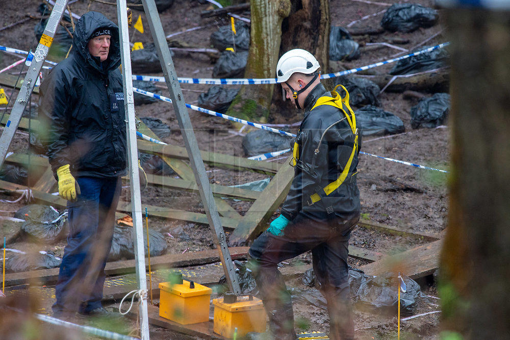 © Licensed to London News Pictures. 17/12/2019. Beaconsfield, UK. A member of the search team wearing a dry suit and a harness and a colleague stand by a tripod hoist stand at an ingress point to what appears to be an underground area. London's Metropolitan Police Service have called in the forces specialist Under Water and Confined Space Search Team as they continue to search woodland in Beaconsfield. The Met confirmed on 12th December 2019 they are searching the woodland in Beaconsfield, Buckinghamshire in connection with the disappearance and murder of Mohammed Shah Subhani. Police have been in the area conducting operations on Hedgerley Lane since Thursday 5th December 2019 and are combing wooded area with specialist officers assisted by specialist search dogs. Photo credit: Peter Manning/LNP
