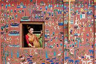 A young Laotian woman poses for engagement photos at Wat Xienghtong in Luang Prabang.