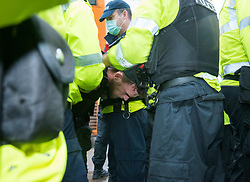 © Licensed to London News Pictures; 14/11/2020; Bristol, UK. Police restrain and arrest a man at an Anti-Lockdown protest march and rally by Stand Up Bristol and StandUpX2, against the Covid-19 lockdown during the coronavirus pandemic, taking place on College Green in front of Bristol City Hall. Protests have been declared illegal under the current Covid-19 lockdown as people are not allowed to meet in more than groups of two and police have threatened arrests and fines against those attending. Police arrested several people. The protest is against Lockdowns, Isolation of the Elderly, Ruined Childhoods, Business Closures, Masks, Government Interference in Private Life and is part of a series of protests today in Sheffield, Wolverhampton, Portsmouth, Bristol and Bournemouth. England is under a national lockdown, sometimes known as lockdown 2.0, as the UK Government tries to stop the spread of the covid-19 coronavirus pandemic. From 05 November lockdown restrictions came into force across England with all pubs, bars, restaurants and entertainment venues shut as well as all non-essential shops. People have been told to stay at home except for work, education, exercise or essential shopping and each person can only meet one other person from outside their household in an outdoors public space. Photo credit: Simon Chapman/LNP.