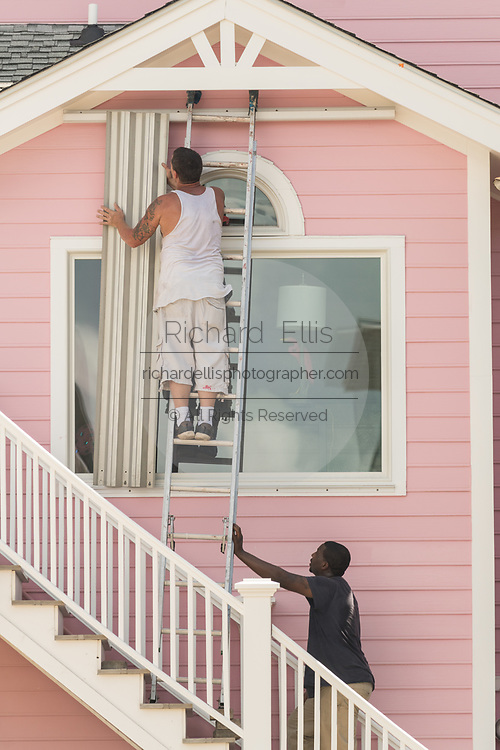 Workers attach hurricane shutters to windows along the beach in preparation for approaching Hurricane Florence September 11, 2018 in Isle of Palms, South Carolina. Florence, a category 4 storm, is expected to hit the coast between South and North Carolina and could be the strongest storm on record for the East Coast of the United States.