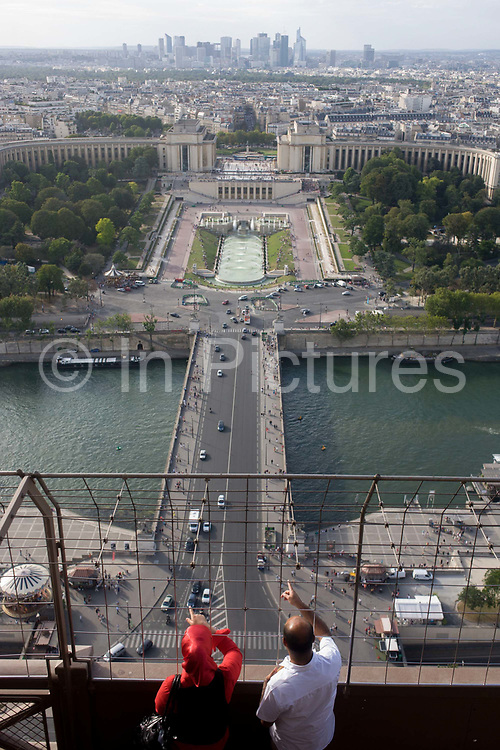 Tourists point out landmarks from the second level of the Eiffel Tower, Paris. Looking towards the trocadero on the opposite bank, the woman wears a hejab and gazes in the same direction as the male. In the far distance is the tall Defense development. The Eiffel Tower (nickname La dame de fer, the iron lady) is a puddled iron lattice tower standing 320 metres (1,050 ft) tall, about the same height as an 81-story building. It is located on the Champ de Mars in Paris, named after the engineer Gustave Eiffel, whose company designed and built the tower. Erected in 1889 as the entrance arch to the 1889 World's Fair, it has become both a global cultural icon of France and one of the most recognizable structures in the world.