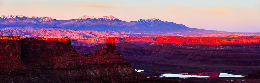 Warm light from the setting sun highlights canyon rims overlooking potash drying pools on the Colorado River near Moab, Utah. The La Sal Mountains are visible in the distant background.<br /> WATERMARKS WILL NOT APPEAR ON PRINTS OR LICENSED IMAGES.