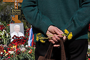 Moscow, Russia, 26/04/2007..Russians visit Boris Yeltsin's grave to pay their last respects after Novodevichy Cemetery was  reopened to the public on the day following the former Russian President's funeral. An old woman holds wild daises she brought to lay at the grave..